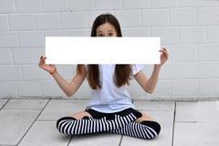 Muchacha que sostiene el cartel en blanco Foto de archivo libre de regalías