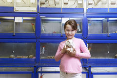 Muchacha que sostiene el conejillo de Indias en tienda del animal doméstico Imagen de archivo libre de regalías
