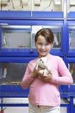 Muchacha que sostiene el conejillo de Indias en tienda del animal doméstico Fotos de archivo