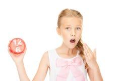 Muchacha que sostiene el despertador Fotos de archivo libres de regalías