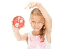 Muchacha que sostiene el despertador Fotos de archivo