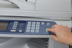 Muchacha que sostiene el finger en la tecla de partida de la impresora laser Fotos de archivo