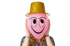 Muchacha que sostiene el globo con la cara y el sombrero sonrientes Fotografía de archivo libre de regalías