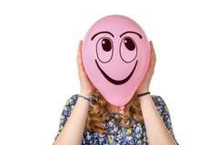 Muchacha que sostiene el globo rosado con la cara sonriente Fotografía de archivo libre de regalías