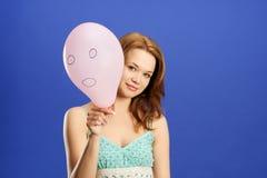 Muchacha que sostiene el globo sorprendido rosado Foto de archivo libre de regalías
