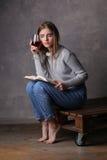 Muchacha que sostiene el libro y el vidrio de vino Fondo gris Imagen de archivo libre de regalías