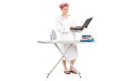 Muchacha que sostiene el ordenador portátil detrás del tablero que plancha Foto de archivo libre de regalías
