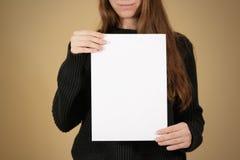 Muchacha que sostiene el papel en blanco blanco A4 Presentación del prospecto Pamphle Imágenes de archivo libres de regalías