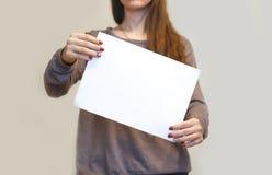 Muchacha que sostiene el papel en blanco inclinado del blanco A4 verticalmente Prospecto pre Fotografía de archivo