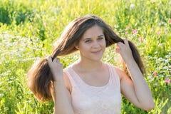 Muchacha que sostiene el pelo largo en prado de la flor Imagen de archivo