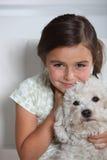 Muchacha que sostiene el pequeño perro Fotos de archivo