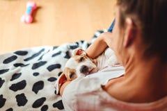 Muchacha que sostiene el perrito soñoliento imagenes de archivo