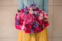 Muchacha que sostiene el ramo de flores rosadas y púrpuras mezcladas Imágenes de archivo libres de regalías