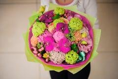 Muchacha que sostiene el ramo de flores rosadas y verdes imagen de archivo libre de regalías