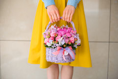 Muchacha que sostiene el ramo rosado hermoso de flores mezcladas en cesta Fotos de archivo