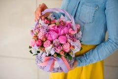 Muchacha que sostiene el ramo rosado hermoso de flores mezcladas en cesta Imágenes de archivo libres de regalías