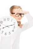 Muchacha que sostiene el reloj grande Foto de archivo