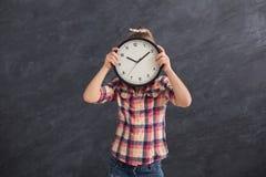 Muchacha que sostiene el reloj grande, cubriendo su cara Foto de archivo
