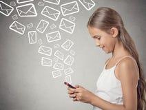 Muchacha que sostiene el smartphone que manda un SMS enviando correos electrónicos Imagen de archivo