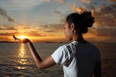 Muchacha que sostiene el sol Fotos de archivo libres de regalías