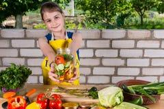 Muchacha que sostiene el tarro llenado de las verduras frescas del corte Foto de archivo