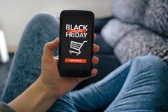 Muchacha que sostiene el teléfono elegante con el concepto de Black Friday en la pantalla fotos de archivo libres de regalías