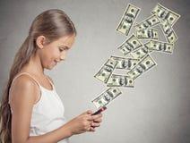 Muchacha que sostiene el teléfono elegante que envía el pago Fotos de archivo libres de regalías