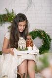 Muchacha que sostiene en sus manos una decoración de la Navidad de la bandeja Fotos de archivo libres de regalías