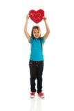 Muchacha que sostiene la almohada del corazón Fotos de archivo libres de regalías