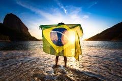 Muchacha que sostiene la bandera brasileña en la playa foto de archivo libre de regalías