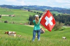 Muchacha que sostiene la bandera suiza Fotos de archivo
