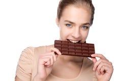 Muchacha que sostiene la barra de chocolate grande en sus tooths fotografía de archivo