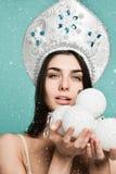 Muchacha que sostiene la bola blanca de la Navidad para adornar el árbol de navidad imagenes de archivo