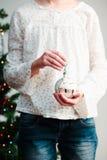 Muchacha que sostiene la bola de la Navidad Fotos de archivo