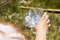 Muchacha que sostiene la botella plástica fotografía de archivo