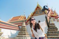 Muchacha que sostiene la cámara y que toma el selfie de la imagen Imágenes de archivo libres de regalías