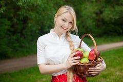 Muchacha que sostiene la cesta con las manzanas rojas y verdes en el parque Imágenes de archivo libres de regalías