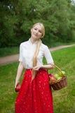 Muchacha que sostiene la cesta con las manzanas rojas y verdes en el parque Fotografía de archivo