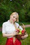Muchacha que sostiene la cesta con las manzanas rojas y verdes en el parque Foto de archivo libre de regalías