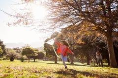 Muchacha que sostiene la cometa mientras que corre en el parque Fotos de archivo