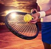 Muchacha que sostiene la estafa y la bola de tenis en el cielo azul Fotografía de archivo libre de regalías