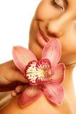 Muchacha que sostiene la flor de la orquídea en sus manos Imágenes de archivo libres de regalías