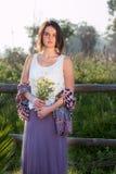 Muchacha que sostiene la flor salvaje al aire libre Fotografía de archivo