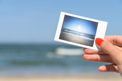 Muchacha que sostiene la foto inmediata de la playa del mar Fotografía de archivo libre de regalías