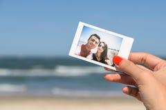 Muchacha que sostiene la foto inmediata de pares felices Imagen de archivo libre de regalías