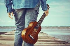 Muchacha que sostiene la guitarra del ukelele en el puente de madera Fotografía de archivo