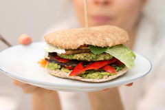 Muchacha que sostiene la hamburguesa deliciosa del vegano en la placa blanca disponible Foto de archivo