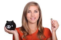 Muchacha que sostiene la hucha Imagenes de archivo