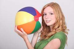 Muchacha que sostiene la pelota de playa Foto de archivo libre de regalías