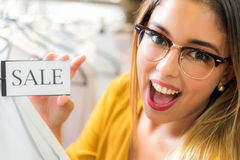 Muchacha que sostiene la pequeña cartulina de las ventas de la ropa fotos de archivo
